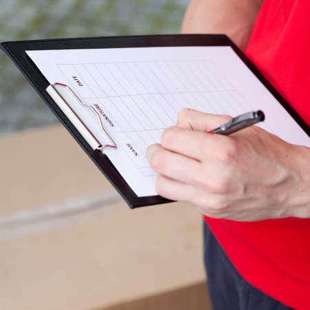 portapapeles: Primer plano de un hombre de entrega que completan el documento de transporte