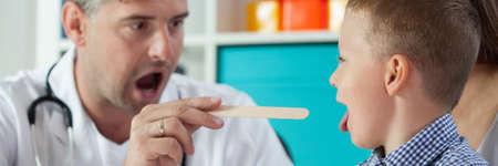 pediatrist: Pediatrist examinate young boy throat with sick