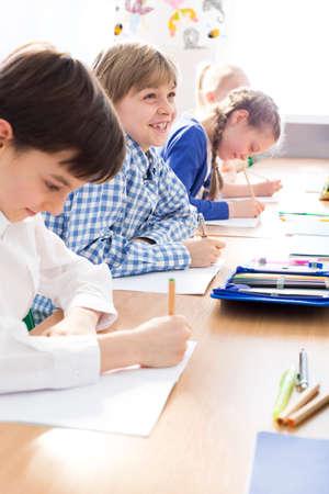 trabajando duro: Felices los niños que trabajan duro que tienen trabajo individual durante la lección en la escuela. Todo el mundo a escribir una prueba Foto de archivo