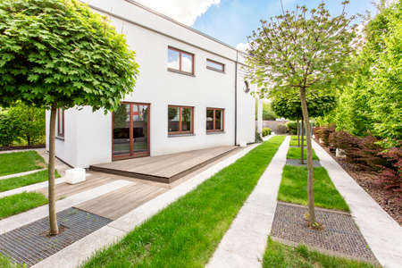 White modern villa with green lawn, decorative pathways and small trees