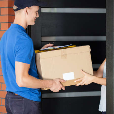 homeowner: Delivery man giving parcel to homeowner, vertical Stock Photo