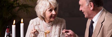 mujeres elegantes: feliz pareja mayor que come elegante cena en el restaurante