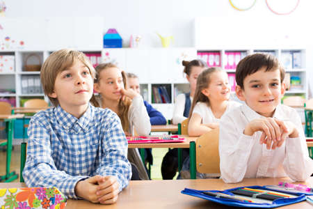 first day: Group of little happy kids at their first day at school. Sitting in pairs in school bends