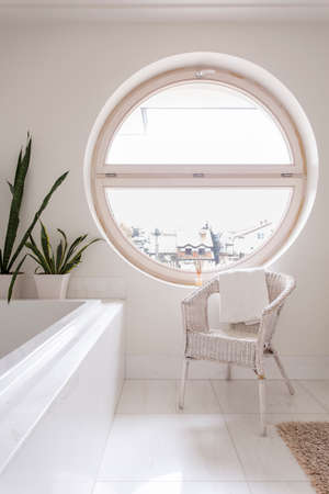round window: Spacious bathroom with white tiling, bathtub, chair and round window
