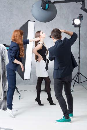 Móda zasedání ve fotografickém studiu s modelem v černé a bílé šaty, fotograf a jeho asistent