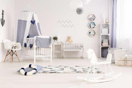 Helles und geräumiges Babyzimmer im maritimen Stil mit stilvollen Navy-Dekorationen