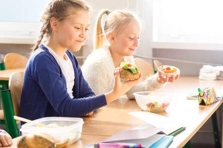 niño escuela: Dos niñas bonitas que comen bocadillos saludables juntos durante el almuerzo en la escuela
