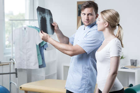 color therapist: Young physiotherapist and his patient looking at xray photo