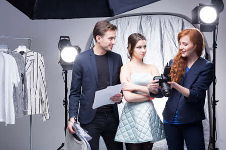 fashion shoot: Young female photographer showing photos in the camera to a designer and his model in a photographic studio Stock Photo