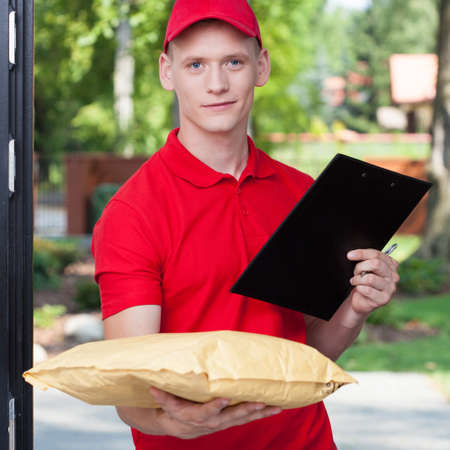 courier: Handsome young courier bringing a package, vertical
