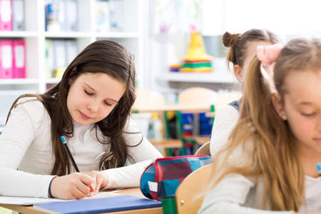 essay: Young girl writing an essay during lesson. Pretty girl trying to be a good student