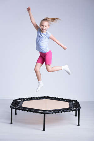 Happy school girl jumping on a small trampoline in a very bright room