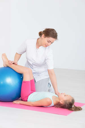 body posture: Friendly physiotherapist working on little girls body posture, using an exercise ball