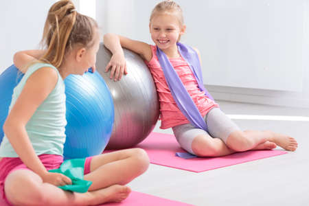 Two little friends resting against large exercise balls after finished exercises, smiling and chatting Stock Photo