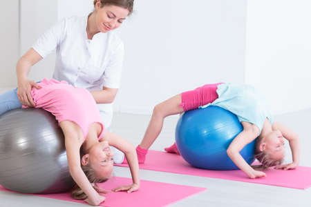 physical therapist: Two smiling girls stretching their back on exercise balls, instructed by a physiotherapist Stock Photo