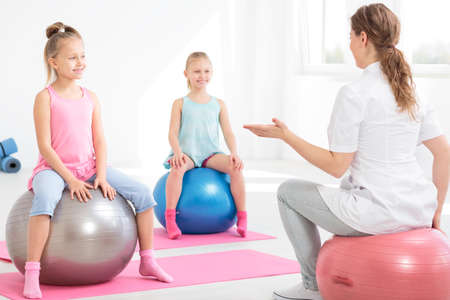 posture correction: Young physiotherapist explaining exercises to smiling school girls sitting on exercise balls Stock Photo
