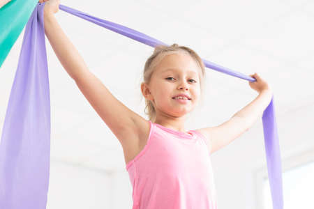 posture correction: Close-up of a smiling little girl exercising with a violet resistance band in a very bright room