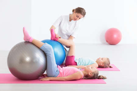 physical therapist: Two school girls lying on exercise mats exercising their legs on balls, accompanied by a physical therapist