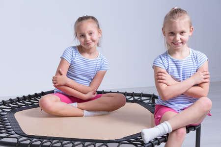 niñas pequeñas: Dos niñas alegres vestidos con la misma ropa de deportes, sentado en un pequeño trampolín en una habitación luminosa