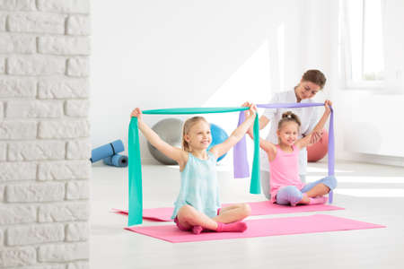 posture correction: Two school girls doing exercises with resistance bands, supervised by a physiotherapist Stock Photo