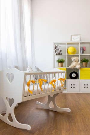 Shot van een wieg in een moderne witte en gele babykamer