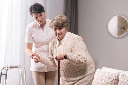 Mujer con bastón asistido por cuidador joven.