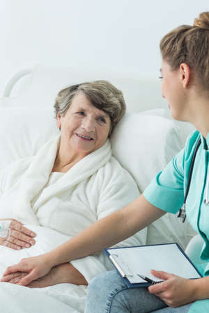 elderly woman: Young nurse with notes holding senior patients hand. Elderly woman lying in bed, smiling.