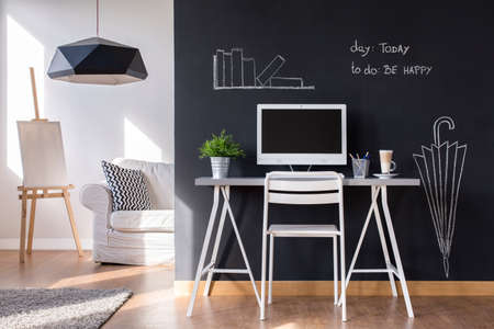 Minimalist modern work space at home with blackboard wall