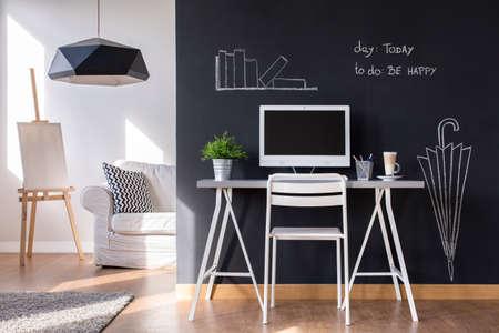 Minimalista espacio de trabajo moderno en el hogar con la pared de la pizarra