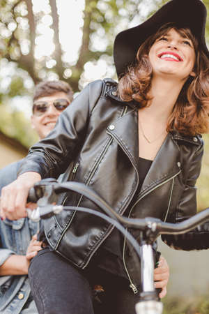 boy lady: Young couple is riding on a bike and smiling