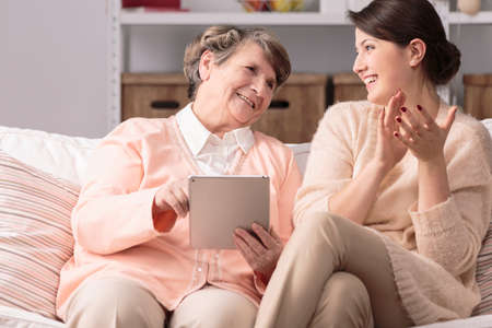 home care: Senior woman with tablet sitting on sofa next to her happy granddaughter. Stock Photo