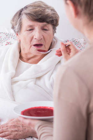 afflictions: Woman feeding senior patient  lying in bed.