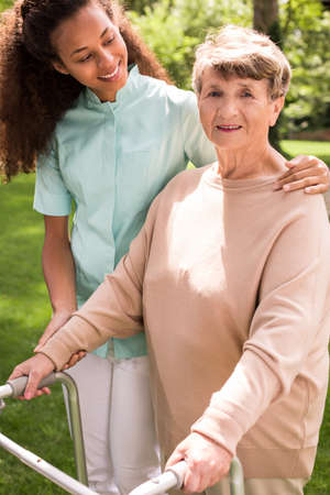 helpful: Image of helpful caregiver with senior in the garden Stock Photo