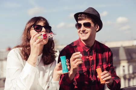 burbujas de jabon: Pareja joven deja burbujas de jab�n en un d�a soleado