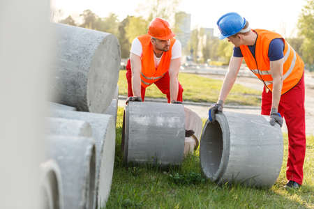 construction workers: Building workers with large concrete pipes
