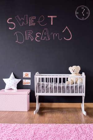 baby nursery: Pink sweet dreams writing on blackboard wall in nursery room Stock Photo