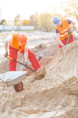 hardworking: Construction workers loading the sand with shovels