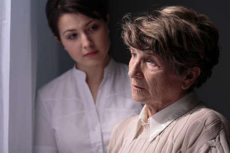 Sad senior woman and good, young carer. Zdjęcie Seryjne