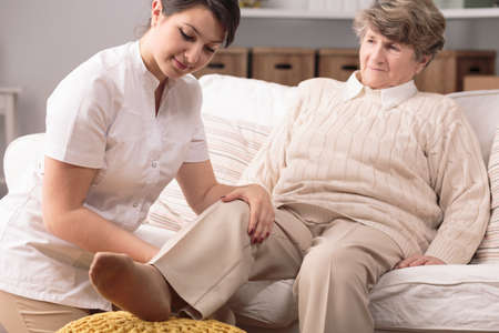 afflictions: Young physiotherapist and senior woman sitting on sofa during exercises.