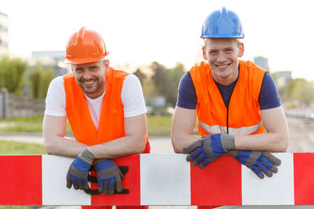 construction site helmet: Happy smiling construction workers looking into the camera