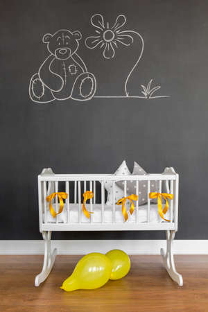 Shot van een kinderbedje in een babykamer met een krijtbord muur