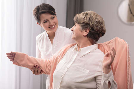 cheerfulness: Positive senior woman assisted by young, smiling carer.