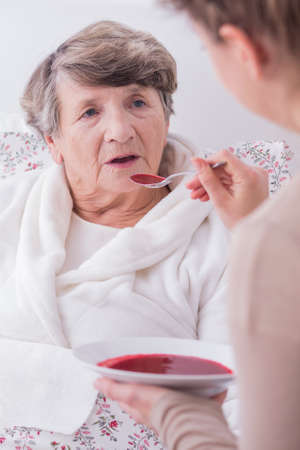 afflictions: Daughter feeding her mother. Sad senior woman lying in bed.
