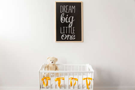nursery room: Shot of a crib with a teddy bear and a blackboard on a wall in a nursery room Stock Photo