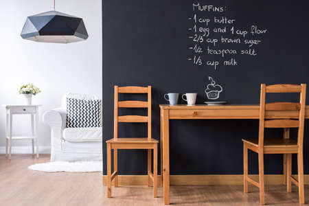 room: Small minimalist dining room with modern blackboard wall Stock Photo