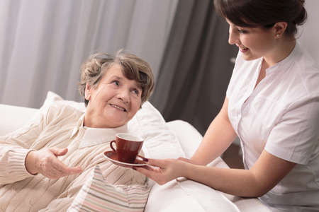 afflictions: Young carer giving a cup to senior woman sitting on sofa.