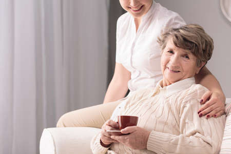 afflictions: Happy senior woman sitting, holding cup. Young carer holding hand on her arm. Stock Photo