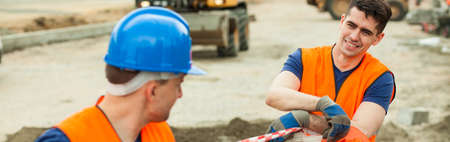 sidewalk talk: Young construction workers have a break during their work Stock Photo