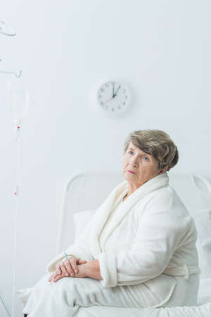 afflictions: Sad senior woman sitting on hospital bed. Interior in white. Stock Photo