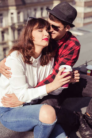 youthfulness: Young man embraces tenderly his girlfriend while they are sitting on a rooftop